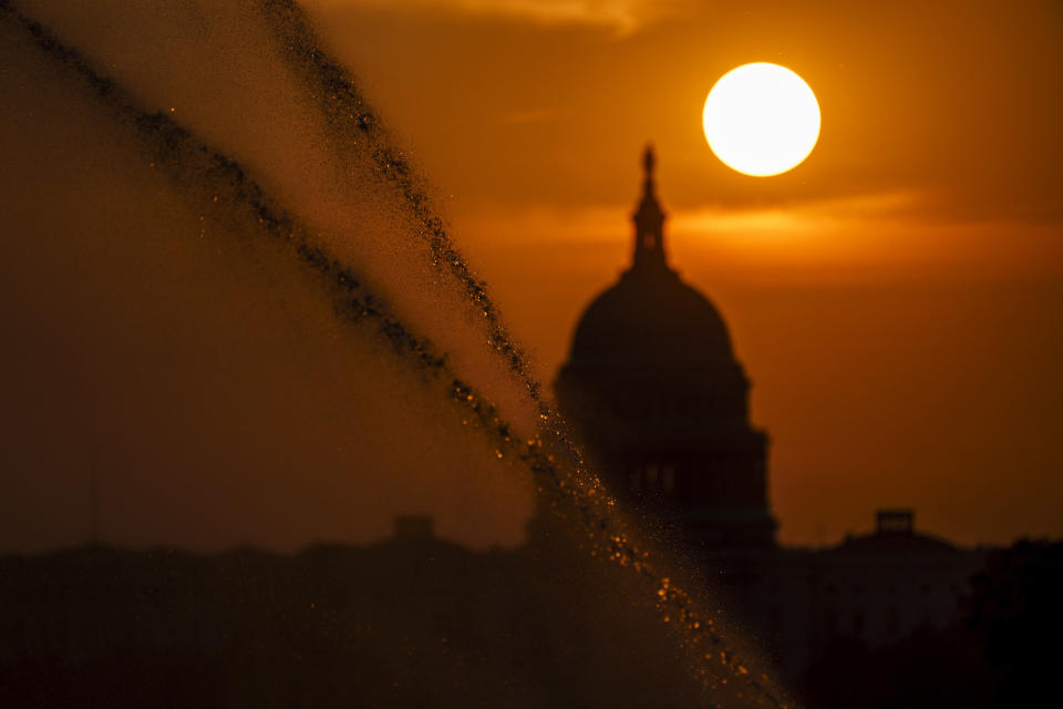 Sprinklers shoot jets of water along the National Mall as the sun rises behind the Capitol in Washington, Wednesday, Sept. 15, 2021. (AP Photo/J. Scott Applewhite)