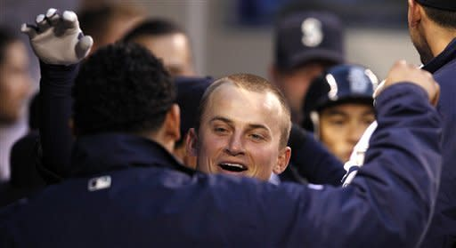 Seattle Mariners' Kyle Seager smiles as he is hugged by starting pitcher Felix Hernandez in the dugout after hitting a two-run home run against the Minnesota Twins in the seventh inning of a baseball game, Saturday, May 5, 2012, in Seattle. (AP Photo/Elaine Thompson)