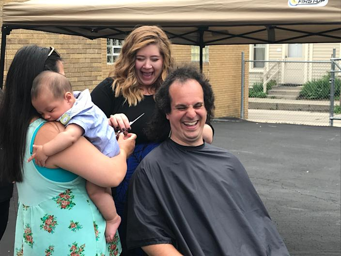 State Rep. Jonathan Brostoff, D-Milwaukee, laughs as he gets his bushy hair cut after a sign language interpreter bill he supported passed the Wisconsin Legislature.