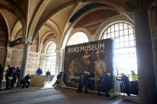 """Workers push a container bearing the painting """"The Night Watch"""" by Rembrandt in the Rijksmuseum, March 27, 2013"""