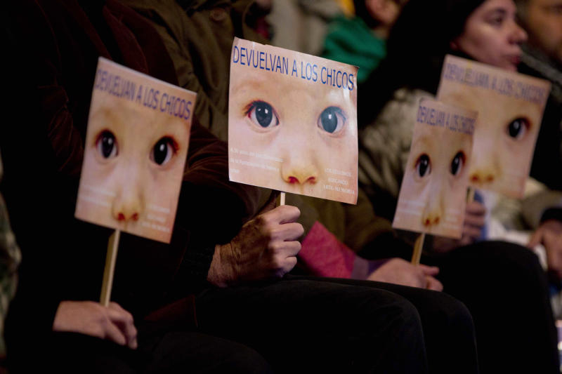 "People hold signs that read in Spanish ""Give the children back"" outside a court where Argentina's historic stolen babies trial is being held in Buenos Aires, Argentina, Thursday, July 5, 2012. Former dictators Jorge Videla and Reynaldo Bignone and a handful of other retired military and police officials are accused of systematically stealing babies from leftists who were kidnapped and killed when a military junta ran the country three decades ago. (AP Photo/Natacha Pisarenko)"