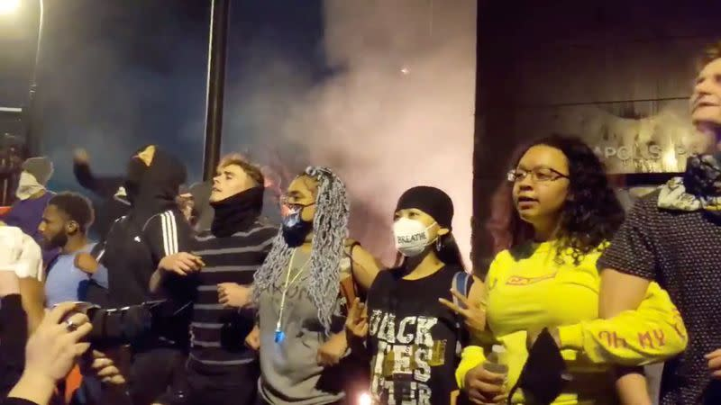Protesters gather around an on fire entrance of a police station, in Minneapolis