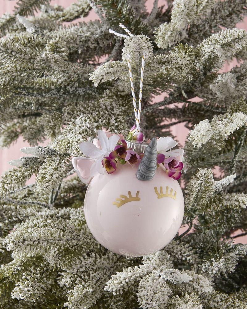 """<p>Delight the kids and grandkids with this sweet and friendly DIY unicorn ornament</p><p><strong>To make:</strong> Remove the cap from a glass or plastic ball ornament. Lightly water down a small amount of light pink acrylic paint. Carefully pour the paint in the opening of the ornament. Rotate the ornament until the inside is fully covered with paint; pour out excess. Allow to dry then reattach cap. Press desired color sculpting clay into a silicone unicorn mold to create ears and horn; allow to dry completely. Attach a mini unicorn horn, ears, and fake flowers with hot glue. Draw eyelashes just below the horn with a gold paint pen.</p><p><a class=""""link rapid-noclick-resp"""" href=""""https://www.amazon.com/Decorating-Fondant-Icing-Silicone-Mould/dp/B07G4CY7M6/ref=sr_1_6?tag=syn-yahoo-20&ascsubtag=%5Bartid%7C10050.g.1070%5Bsrc%7Cyahoo-us"""" rel=""""nofollow noopener"""" target=""""_blank"""" data-ylk=""""slk:SHOP UNICORN MOLD"""">SHOP UNICORN MOLD</a></p>"""