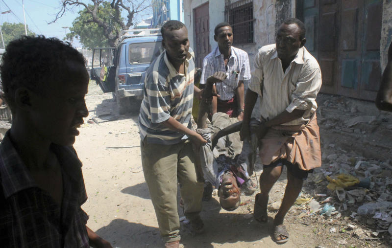 Somalis carry away the body of a man said to be the suicide car bomber who appeared to be targeting a convoy of African Union and Somali troops in Mogadishu, Somalia Friday, Dec. 14, 2012. A Somali police official says a suicide car bomb explosion in Mogadishu killed only the bomber but wounded three bystanders when the car exploded. (AP Photo/Farah Abdi Warsameh)