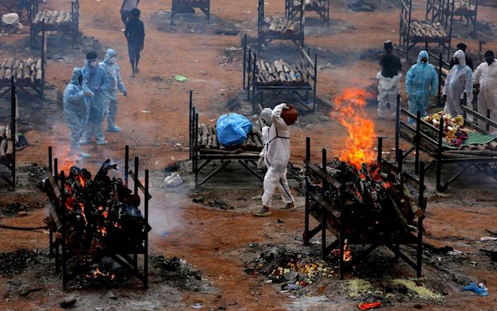 Relatives perform the last rites for Covid-19 victims during their funeral at a mass cremation ground in the outskirts of Bangalore - Jagadeesh NV/Shutterstock