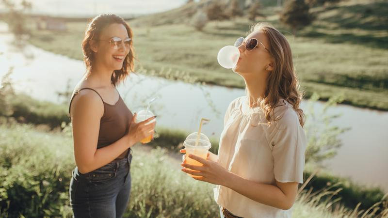two beautiful girlfriends have fun blowing up a bubble from chewing gum, drinking orange juice in plastic cup, in sunglasses, summer, at sunset, positive facial expression, outdoor.