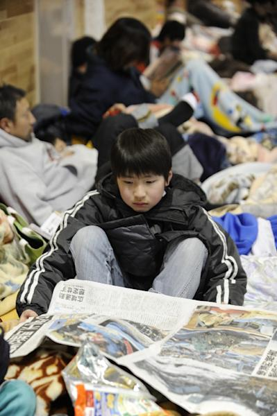 A boy reads a newspaper article on the earthquake at a shelter for evacuees in the town of Minamisoma in Fukushima Prefecture on March 12, 2011 (AFP Photo/Kazuhiro Nogi)
