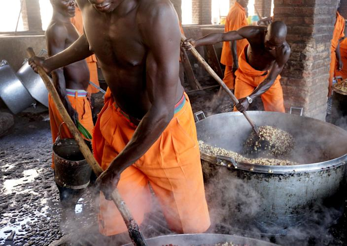 Prisoners cook corn at Rwamagana Prison in Rwamagana, Rwanda, on November 18, 2017. All of Rwanda's prisons use their prisoners' waste - in addition to that of cows - to fuel their kitchens via biogas. At Rwamagana, biogas is used to cook corn, and peat cooks rice and beans. Many prisoners say they can usually tell when biogas is used due to the lack of smokey flavor in food. (Photograph by Yana Paskova)