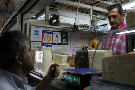 Information for Vippo app and other methods of payment is seen at a cheese and dairy products stall at Chacao Municipal Market in Caracas, Venezuela January 19, 2018. REUTERS/Marco Bello