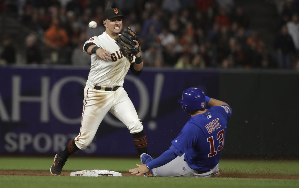 San Francisco Giants second baseman Joe Panik, left, throws to first base after forcing Chicago Cubs' David Bote (13) at second base on a double play hit by Addison Russell during the ninth inning of a baseball game in San Francisco, Tuesday, July 23, 2019. (AP Photo/Jeff Chiu)