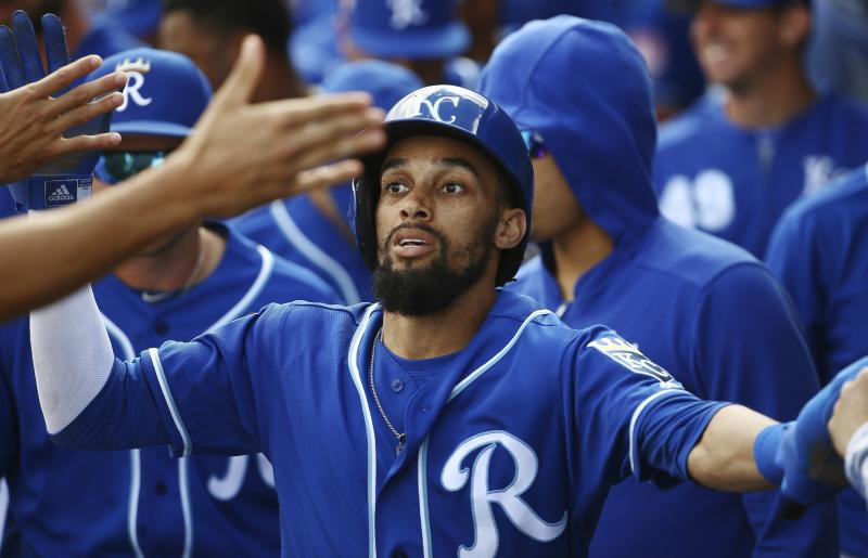 Kansas City Royals' Billy Hamilton celebrates his run scored against the Cincinnati Reds with teammates in the dugout during the first inning of a spring training baseball game Friday, March 8, 2019, in Surprise, Ariz. (AP Photo/Ross D. Franklin)