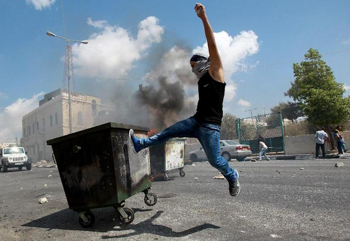 A masked Palestinian youth kicks a garbage container during clashes with Israeli security forces on September 21, 2015 at the main entrance of the West Bank city of Bethlehem (AFP Photo/Musa al-Shaer)