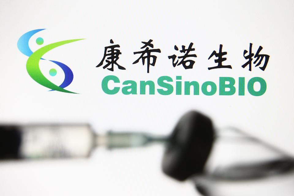 UKRAINE - 2021/02/06: In this photo illustration a CanSinoBIO also known as CanSino Biologics, a Chinese vaccine company, logo is seen in front of a vial and a medical syringe. China has approved the Sinovac Biotech COVID-19 vaccine against coronavirus for use by the general public reported by the media. (Photo Illustration by Pavlo Gonchar/SOPA Images/LightRocket via Getty Images)
