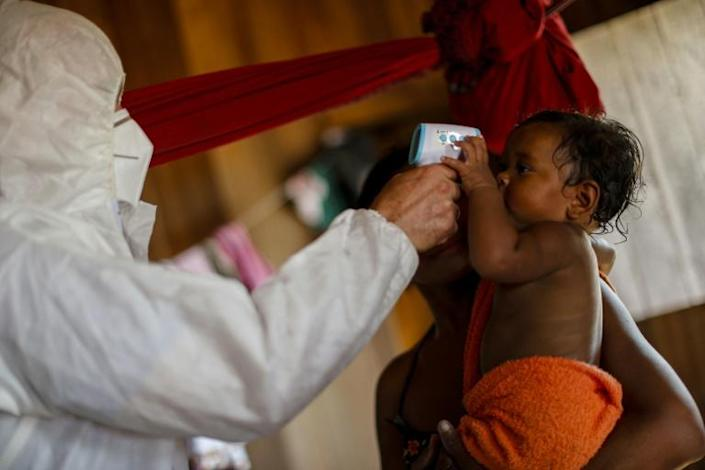 A health worker measures the temperature of riverside residents at the Pindobal community in the Igarape-Miri municipality, Para state, Brazil