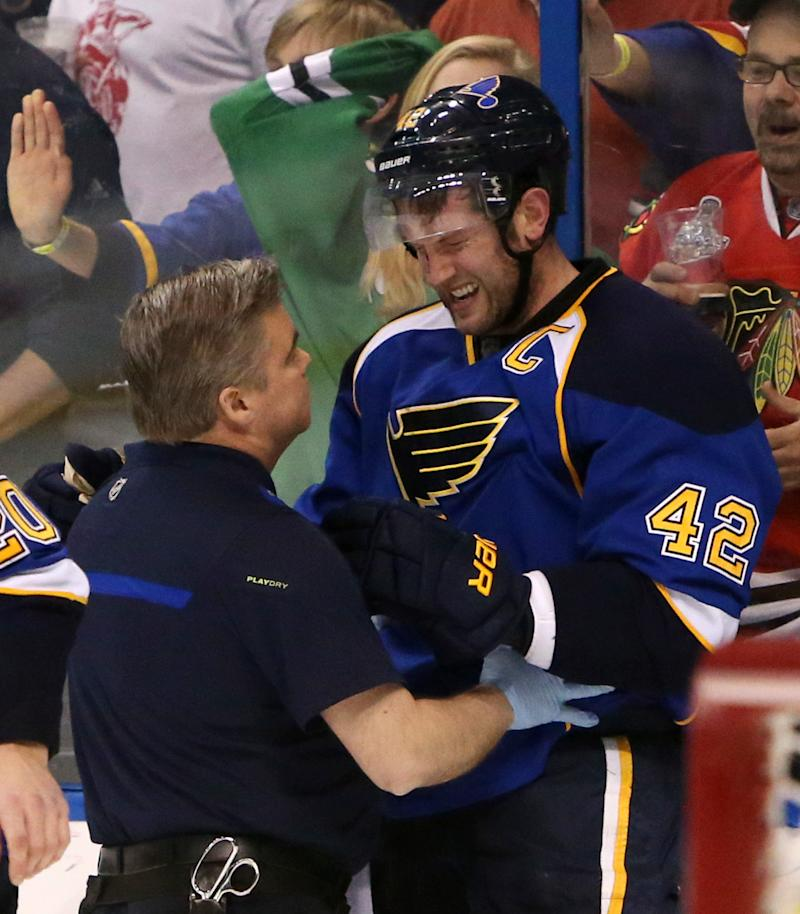 St. Louis Blues center David Backes (42) is tended to by trainer Ray Barile after taking a hit from Chicago Blackhawks defenseman Brent Seabrook in the third period during Game 2 of a first-round NHL hockey playoff series on Saturday, April 19, 2014, in St. Louis. Seabrook was assessed a game misconduct penalty for the play and the Blues scored the tying goal on the ensuing five-minute power play. Backes left the ice under his own power
