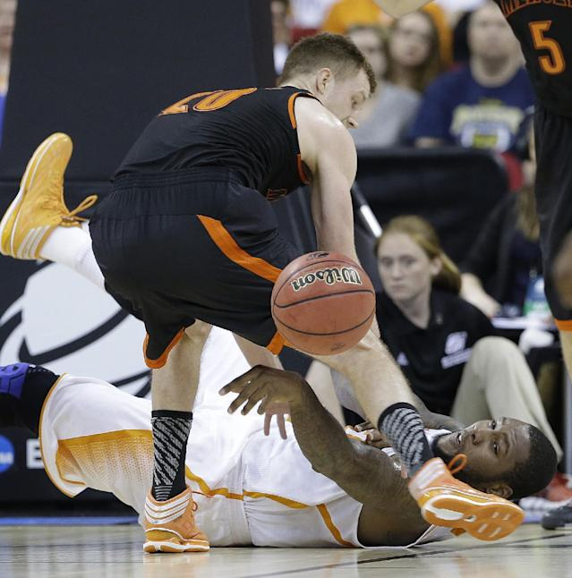 Tennessee forward Jeronne Maymon (34) passes the ball against Mercer forward Jakob Gollon (20) during the first half of an NCAA college basketball third-round tournament game, Sunday, March 23, 2014, in Raleigh. (AP Photo/Gerry Broome)
