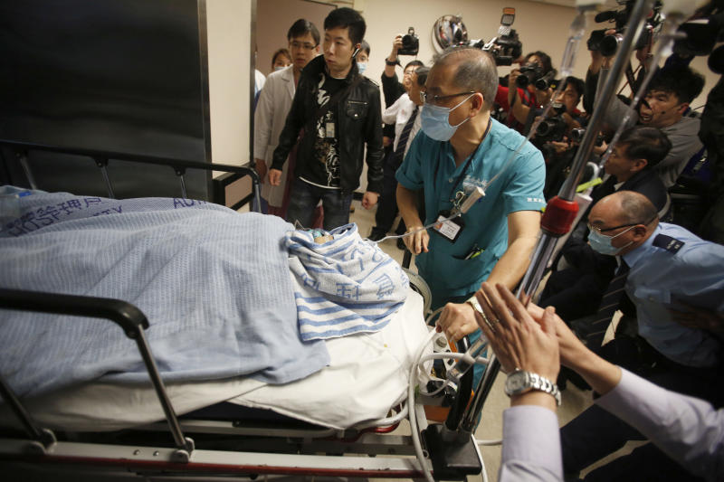 "Medical staffs escort former Ming Pao chief editor Kevin Lau on a stretcher in a hospital in Hong Kong, China Wednesday, Feb. 26, 2014. The former editor of the Hong Kong newspaper whose abrupt dismissal in January sparked protests over press freedom has been stabbed, police said on Wednesday. Police said a man wearing a motorcycle helmet ""suddenly"" attacked Kevin Lau on Wednesday morning with a knife and then fled on a motorcycle driven by another man. (AP Photo)"