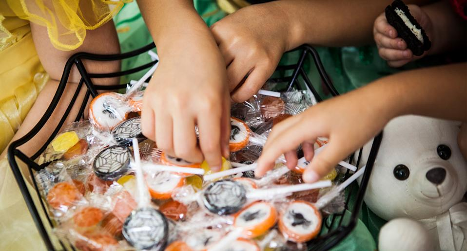 Kids grabbing from a lolly basket after needles were found in Halloween treats.