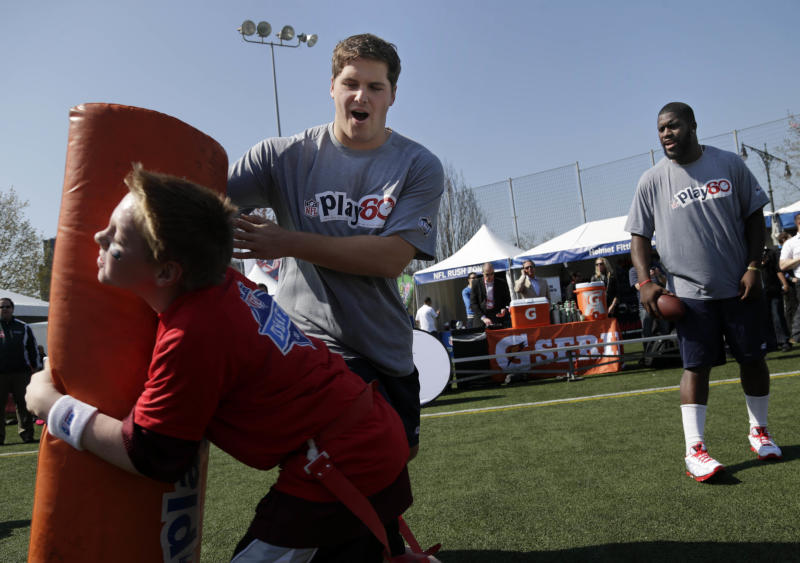 NFL draft prospects Luke Joeckel of Texas A&M, rear left, and Menelik Watson of Florida State, right, participate in a youth football clinic in New York, Wednesday, April 24, 2013. The draft begins Thursday in New York. (AP Photo/Seth Wenig)