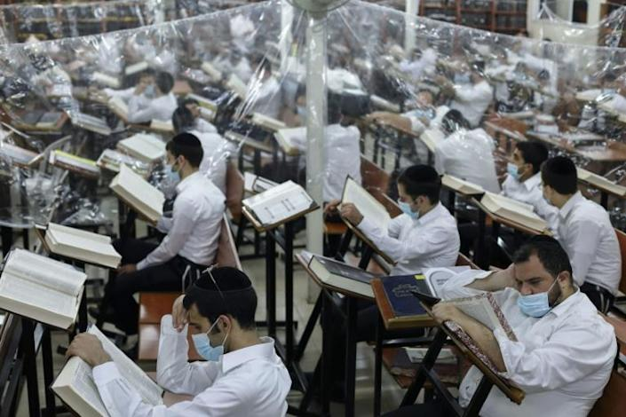 Ultra-Orthodox Jewish men study in a hall divided with plastic sheets to help slow the spread of Covid-19 in the religious city of Bnei Brak near Tel Aviv