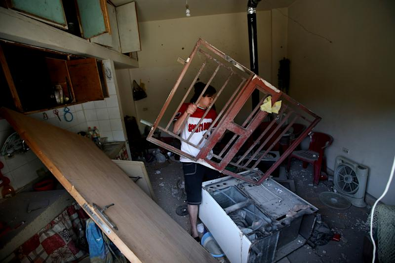 A Lebanese man removes debris, after a rocket fire by Syrian rebels and hit his home, according to villagers, in Hermel town, northeast of Lebanon, Wednesday May 29, 2013. Shells fire from Syria regularly strike the Lebanese northeastern town of Hermel, a predominantly Shiite town. Sectarian tensions in Lebanon have been on the rise, particularly as a result of the involvement of the militant Hezbollah group in fighting in Syria alongside President Bashar Assad's forces. (AP Photo/Hussein Malla)