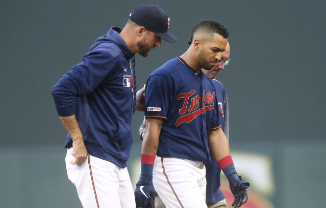 Minnesota Twins' Eddie Rosario, center, is helped off the field by manager Rocco Baldelli, left, and trainer Tony Leo following an injury after he rounded first base on a hit during the third inning of the team's baseball game against the Tampa Bay Rays on Wednesday, June 26, 2019, in Minneapolis. (AP Photo/Jim Mone)