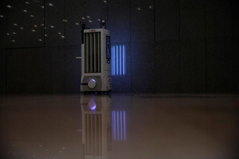 A self-driving robot sanitizes a wall with UV light during its demonstration at the headquarters of SK Telecom in Seoul