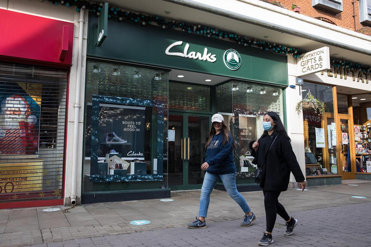 Two women walk past a branch of Clarks, one of the UK's oldest shoe chains
