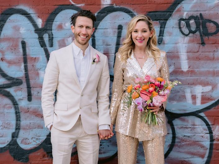 wedding pictures of jen glantz and her husband in front of brick, graffitied wall