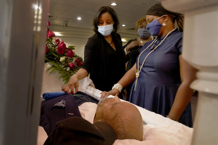 Tara Knox Stockdale, left and her younger sister, Tawane Knox, right, attend to their father, Hosea Knox, at his funeral Monday, Sept. 13, 2021, in Chicago. The elder Knox, owner of Elmo's Tombstones Service, served the predominately Black community in their time of need for more than 33 years. (AP Photo/Charles Rex Arbogast)