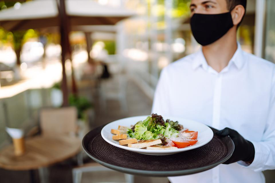 Salad on a waiter's tray. Young  waiter wearing protective face mask while working in reopened cafe after coronavirus epidemic. Covid- 2019.