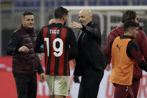 AC Milan's manager Stefano Pioli congratulate his teammate AC Milan's Theo Hernandez for his goal against Lazio during a Serie A soccer match between AC Milan and Lazio, at the San Siro stadium in Milan, Italy, Wednesday, Dec. 23, 2020. (AP Photo/Luca Bruno)