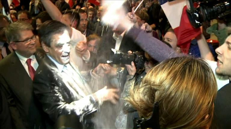French presidential election candidate for the right-wing Les Republicains party Francois Fillon (C) reacts as a man throws flour at him on April 6, 2017 during a political rally in Strasbourg