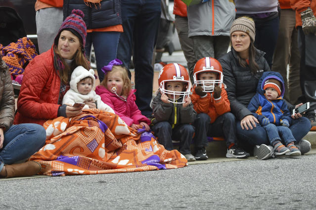 A family enjoys the parade held in Clemson's honor Saturday, Jan. 12, 2019, in Clemson, S.C., TheTigers defeated Alabama 44-16 in the College Football Playoff championship game Monday Jan. 7. (AP Photo/Richard Shiro)