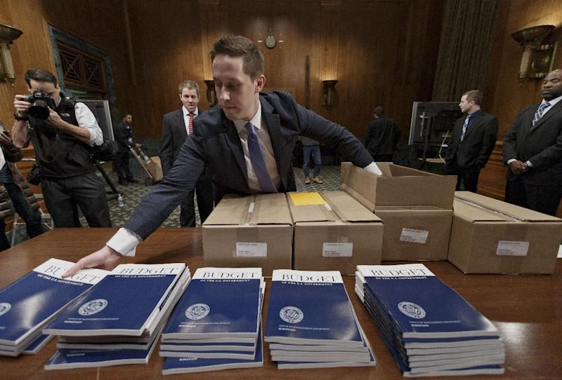 Copies of President Barack Obama's proposed budget for fiscal 2015 are set out for distribution by Senate Budget Committee Clerk Adam Kamp, on Capitol Hill in Washington, Tuesday, March 4, 2014. Obama's fiscal blueprint, which he is sending Congress today, was expected to include proposals to upgrade aging highways and railroads, finance more pre-kindergarten programs and enhance job training. (AP Photo/J. Scott Applewhite)