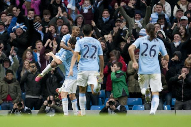 Manchester City's Fernandinho, top left, celebrates with teammates after scoring against Arsenal during their English Premier League soccer match at the Etihad Stadium, Manchester, England, Saturday Dec. 14, 2013. (AP Photo/Jon Super)