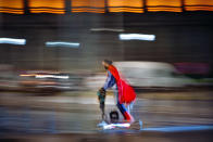 A man wearing a superhero costume rides a scooter in Bucharest, Romania, Friday, Oct. 23, 2020. In much of Europe, city squares and streets, be they wide, elegant boulevards like in Paris or cobblestoned alleys in Rome, serve as animated evening extensions of drawing rooms and living rooms. As Coronavirus restrictions once again put limitations on how we live and socialize, AP photographers across Europe delivered a snapshot of how Friday evening, the gateway to the weekend, looks and feels. (AP Photo/Vadim Ghirda)