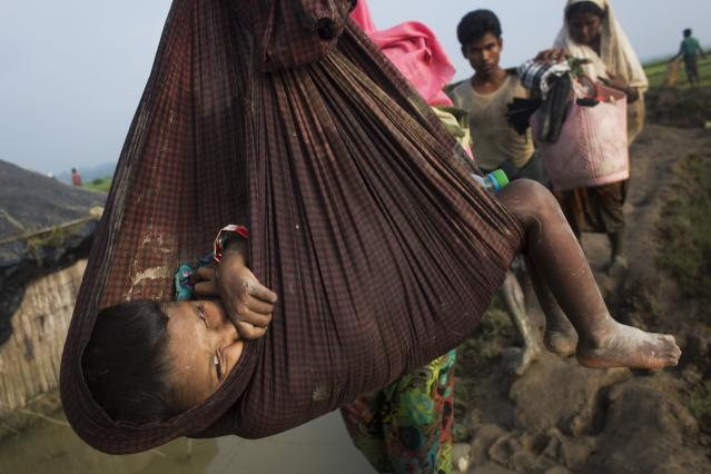 <p>A Rohingya child is carried on a sling while his family walk through rice fields after crossing the border into Bangladesh near Cox's Bazar's Teknaf area, Tuesday, Sept. 5, 2017. (Photo: Bernat Armangue/AP) </p>