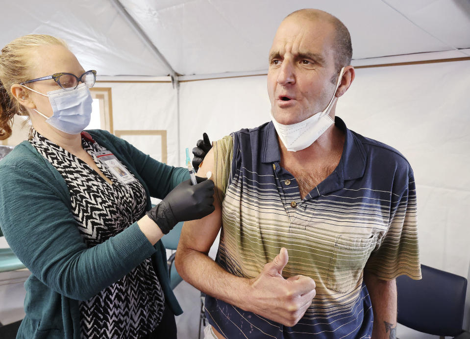 Melissa Mason gives Kenny Collins a COVID-19 vaccination at the Fourth Street Clinic in Salt Lake City on March 23, 2021. Homeless Americans who have been left off priority lists for coronavirus vaccinations — or even bumped aside as states shifted eligibility to older age groups — are finally getting their shots as vaccine supplies increase. (Jeffrey D. Allred/The Deseret News via AP)
