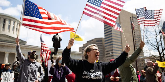 Protesters wave flags outside of the Ohio State House in Columbus, Ohio on April 18, 2020, to protest the stay home order that is in effect until May 1.