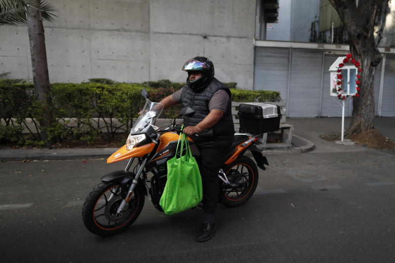 A man on a motorcycle carries groceries in a reusable bag, in Mexico City, Wednesday, Jan. 1, 2020. Stores stopped providing disposable plastic bags to their customers in compliance with a city law that took effect with the new year, and shoppers in Mexico's massive capital city could be seen Wednesday carrying handfuls of loose items, as well as purchases packed into reusable shopping bags or used plastic bags brought from home. (AP Photo/Rebecca Blackwell)