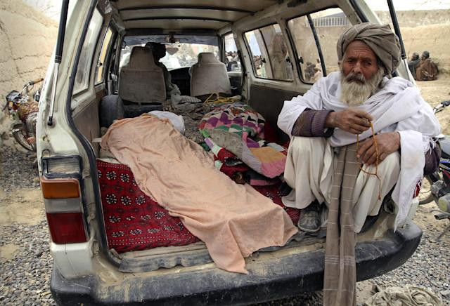An elderly Afghan man sits next to the covered body of a person who was allegedly killed by a U.S. service member, in a minibus in Panjwai, Kandahar province south of Kabul, Afghanistan, Sunday, March 11, 2012. A U.S. service member walked out of a base in southern Afghanistan before dawn Sunday and started shooting Afghan civilians, according to villagers and Afghan and NATO officials. Villagers showed an Associated Press photographer 15 bodies, including women and children, and alleged they were killed by the American. (AP Photo/Allauddin Khan)