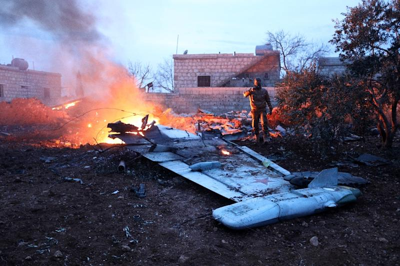 A Syrian rebel fighter takes a picture of a downed Sukhoi-25 fighter jet in Syria's northwest province of Idlib
