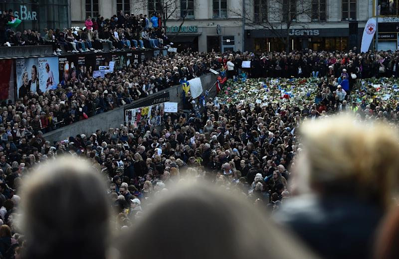 People attend a memorial ceremony on April 9, 2017 at Sergels Torg plaza in Stockholm, Sweden, close to the point where a truck drove into a department store two days before