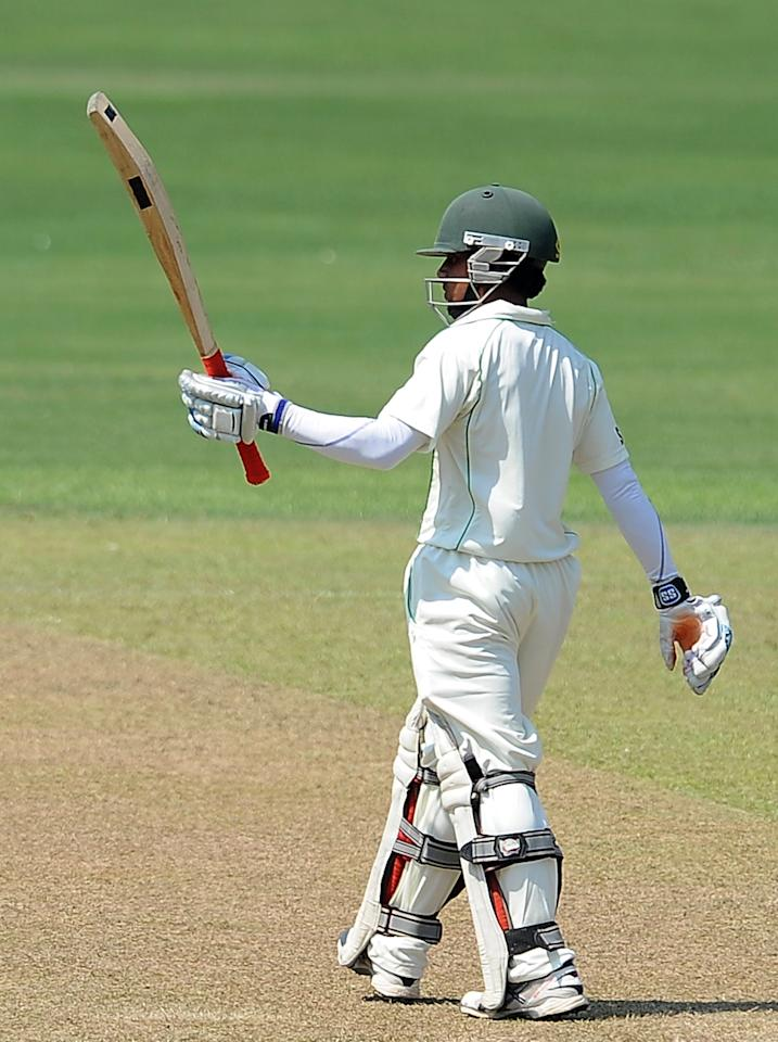 Bangladeshi cricketer Mominul Haque raises his bat to the crowd after scoring a half-century (50 runs) during the opening day of their second Test cricket match between Sri Lanka and Bangladesh at the R. Premadasa Cricket Stadium in Colombo on March 16, 2013.  AFP PHOTO/ LAKRUWAN WANNIARACHCHI