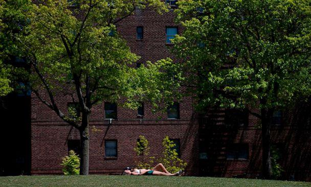PHOTO: A couple enjoys the sun in a park in Queens on May 13, 2020 in New York City. (Johannes Eisele/AFP via Getty Images)