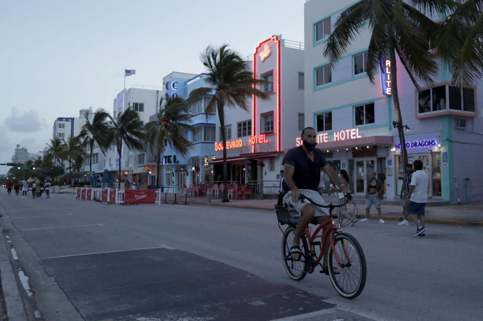FILE - In this July 24, 2020, file photo, a sparse crowd is on Ocean Drive after an 8 p.m. curfew amid the coronavirus pandemic in Miami Beach, Fla. Families trying to get in a last-minute vacation before school starts better do some homework on COVID-19 restrictions before loading up the minivan. (AP Photo/Lynne Sladky, File)