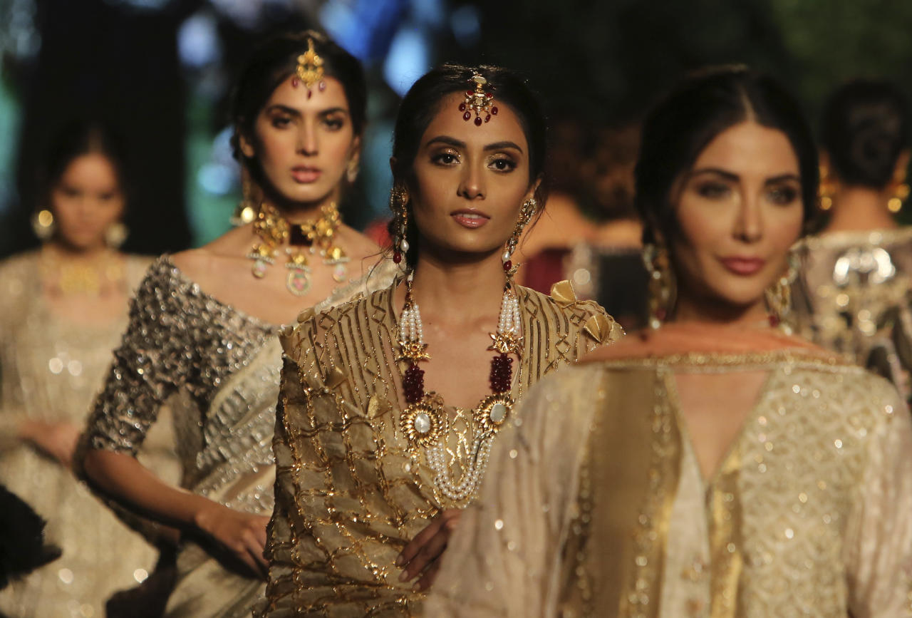 Models present creations by designer Nida Azwer during the Bridal Fashion Week organized by the Pakistan Fashion Design Council in Lahore, Pakistan, Thursday, Sept. 26, 2019. (AP Photo/K.M. Chaudary)