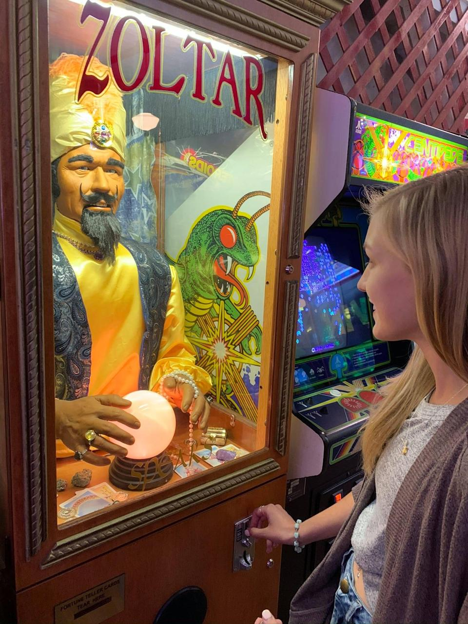 Gabby Petito looks at a mechanical fortune teller in an arcade. (Find Gabby Facebook page)