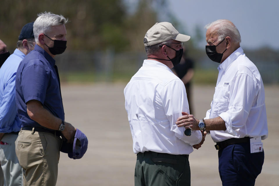 President Joe Biden talks with Louisiana Gov. John Bel Edwards and as Sen. Bill Cassidy, R-La., left, listens as Biden arrives at Louis Armstrong New Orleans International Airport in Kenner, La., Friday, Sept. 3, 2021, to tour damage caused by Hurricane Ida. (AP Photo/Evan Vucci)